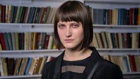 Jeune belle femme avec la coupe de cheveux courte se tenant dans la bibliothèque et regardant l'appareil-photo clips vidéos