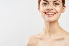 Jeune belle femme avec la découpe pour des plastiques sur le visage sur F-N blanc, sourire, espace vide pour la copie Photos libres de droits
