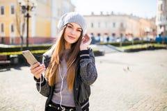 Jeune belle femme avec la musique de écoute de téléphone intelligent dans la ville Images libres de droits