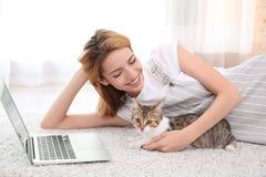Jeune belle femme avec le chat et l'ordinateur portable Images stock