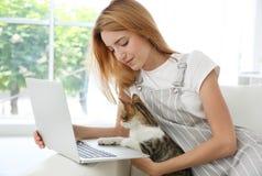 Jeune belle femme avec le chat utilisant l'ordinateur portable Photo stock