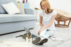 Jeune belle femme avec le chat utilisant l'ordinateur portable Images stock