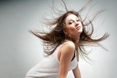 Jeune belle femme avec le cheveu dans le chaos rose de vent Photo libre de droits