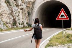 Jeune belle femme avec le sac à dos noir faisant de l'auto-stop la position près du tunnel de route Vue arrière photographie stock