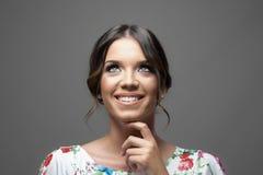 Jeune belle femme avec le sourire parfait recherchant au-dessus du fond gris de studio Photos libres de droits