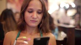 Jeune belle femme avec un téléphone dans un vin de boissons de café 1920x1080 banque de vidéos