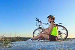 Jeune belle femme avec un vélo de sport, fond mou de foyer photographie stock libre de droits