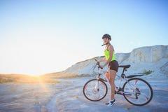 Jeune belle femme avec un vélo de sport, fond mou de foyer photographie stock