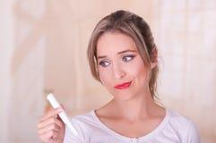 Jeune belle femme avec un visage inquiété, tenant un tampon de coton de règles dans sa main, à un arrière-plan brouillé images stock
