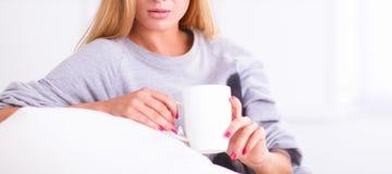Jeune belle femme avec une tasse sur le sofa à la maison photo libre de droits