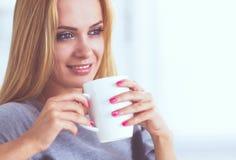 Jeune belle femme avec une tasse sur le sofa à la maison images libres de droits