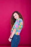 Jeune belle femme ayant l'amusement sur le fond rouge Femelle de sourire Photo stock