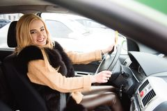Jeune belle femme blonde conduisant sa voiture images stock