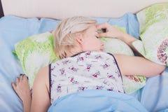 Jeune belle femme blonde dormant dans son lit photographie stock libre de droits