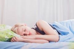 Jeune belle femme blonde dormant dans son lit pendant le matin images libres de droits