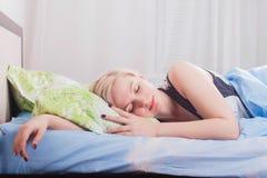 Jeune belle femme blonde dormant dans son lit pendant le matin photos stock