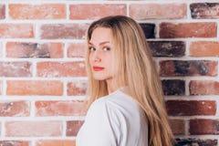 Jeune belle femme blonde gaie heureuse souriant et regardant la cam?ra pr?s du mur de briques photos stock