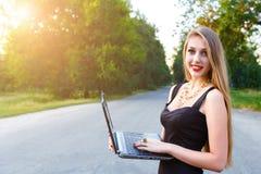 Jeune belle femme blonde tenant un ordinateur portable, fonctionnant dehors image stock
