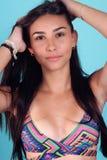 Jeune belle femme bronzée dans le maillot de bain posant sur le fond bleu Photographie stock libre de droits