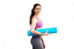Jeune belle femme caucasienne dans le tapis de transport de yoga de vêtements de sport Photos stock