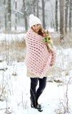 Jeune belle femme caucasienne dans les vêtements et le géant d'hiver tricotant la couverture de rose en pastel Image stock