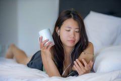 Jeune belle femme chinoise asiatique avec l'écouteur écoutant le mensonge heureux de sourire de musique sur le lit utilisant l'In Image libre de droits