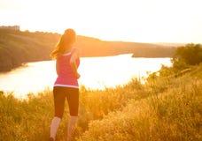 Jeune belle femme courant sur la traînée de montagne pendant le matin Photographie stock