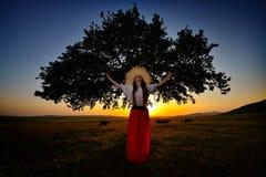 Jeune belle femme détendant sur le champ en été image stock