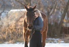 Jeune belle femme d'élégance posant avec le cheval Photographie stock