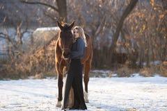 Jeune belle femme d'élégance posant avec le cheval Image stock