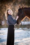 Jeune belle femme d'élégance posant avec le cheval Images stock