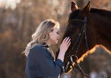 Jeune belle femme d'élégance posant avec le cheval Photo stock