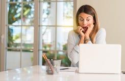 Jeune belle femme d'étudiant avec l'ordinateur portable à la table, à la maison image libre de droits