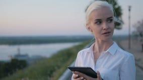 Jeune belle femme d'affaires à l'aide de la tablette dehors sur le coucher du soleil Images stock