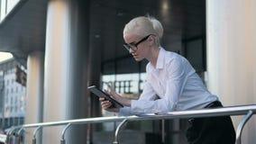 Jeune belle femme d'affaires à l'aide de la tablette en dehors du centre Photographie stock libre de droits