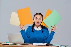 Jeune belle femme d'affaires étonnée s'asseyant sur le lieu de travail, tenant les dossiers colorés Images libres de droits