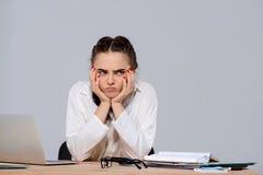 Jeune belle femme d'affaires contrariée s'asseyant sur le lieu de travail au-dessus du fond pourpre Photo stock