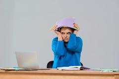 Jeune belle femme d'affaires contrariée s'asseyant sur le lieu de travail, tenant les dossiers colorés Photographie stock libre de droits