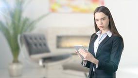 Jeune belle femme d'affaires et concepteur créatif se tenant au-dessus du fond intérieur blured Photographie stock libre de droits
