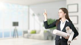 Jeune belle femme d'affaires et concepteur créatif se tenant au-dessus du fond intérieur blured Image stock