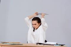 Jeune belle femme d'affaires fâchée s'asseyant sur le lieu de travail au-dessus du fond pourpre Image stock