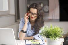 Jeune belle femme d'affaires faisant un téléphone et travaillant au hom image stock