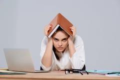 Jeune belle femme d'affaires fatiguée s'asseyant sur le lieu de travail au-dessus du fond pourpre Photo stock