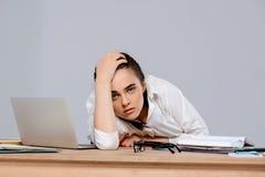 Jeune belle femme d'affaires fatiguée s'asseyant sur le lieu de travail au-dessus du fond pourpre Photographie stock libre de droits
