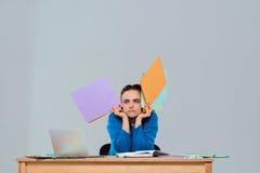 Jeune belle femme d'affaires fatiguée s'asseyant sur le lieu de travail, tenant les dossiers colorés Images libres de droits