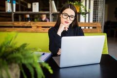 Jeune belle femme d'affaires gaie en verres regardant l'appareil-photo avec le sourire tout en se reposant à son lieu de travail Photo libre de droits