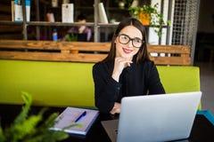 Jeune belle femme d'affaires gaie en verres regardant l'appareil-photo avec le sourire tout en se reposant à son lieu de travail Photos stock