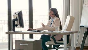Jeune belle femme d'affaires parlant sur le casque dans le bureau banque de vidéos