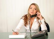 Jeune belle femme d'affaires, retenant le téléphone et écrivant en fonction pas images stock