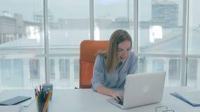 Jeune belle femme d'affaires s'asseyant à une table dans le bureau moderne travaillant à l'ordinateur portable, souriant banque de vidéos